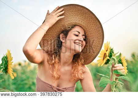 young woman smells perfume of a sunflower