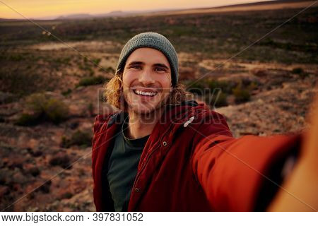 Portrait Of Happy And Smiling Hiker Taking A Selfie On The Top Of The Mountain
