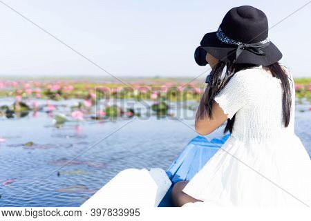 Asian Woman Wearing A White Dress, Wearing A Hat And Sitting On A Blue Boat. Taking Pictures At Lake