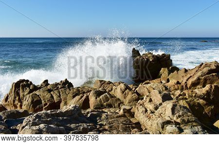 Waves Breaking Against The Rocks With Blue Sky. Rias Baixas, Galicia, Spain.