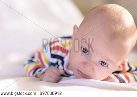 The Child On A Stomach Looks With Curiosity Isolated On White