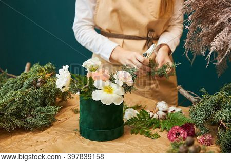 A Female Florist Creates A Bouquet For Christmas From Flowers And Branches Of Spruce. The Work Of A