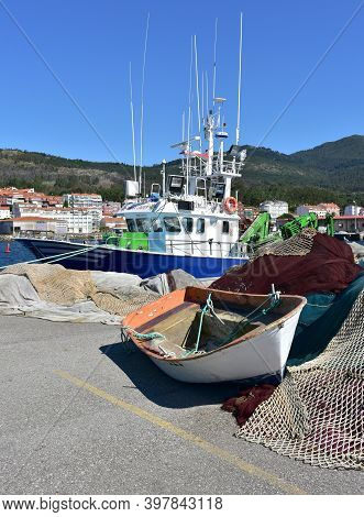 Portosin, Spain. July 3, 2020. Harbor With Galician Fishing Vessel And Old Row Boat. A Coruña Provin