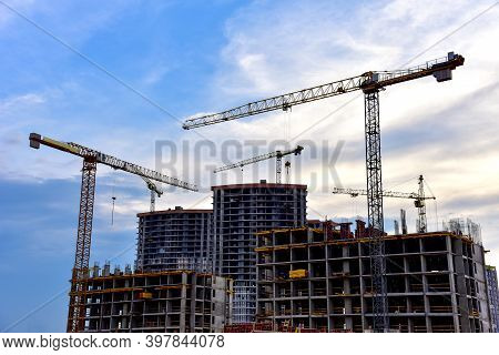 Tower Cranes Working At Construction Site On Blue Sky Background. Construction Process Of The New Mo