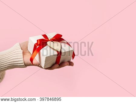 Beauty Woman Hands Holding Gift Box With Red Bow And Heart On Pink Background, Close-up. Pastel Colo