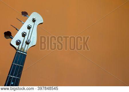 Miercurea Ciuc, Romania- 03 December 2020: Harley Benton Bass Guitar Neck On Orange Background.