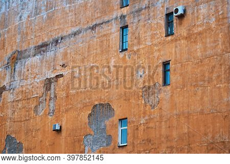 Part Of The Large Plastered Wall Of An Old House With Small Windows And Plenty Of Empty Space For A