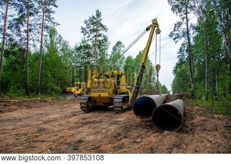 Pipelayer With Side Boom Installation Of Gas And Crude Oil Pipes In Ground. Construction Of The Gas