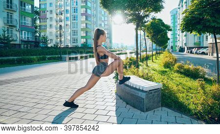 Fitness Woman With Perfect Body Stretching Leg On Bench, Doing Exercises After Running Workout In Ci