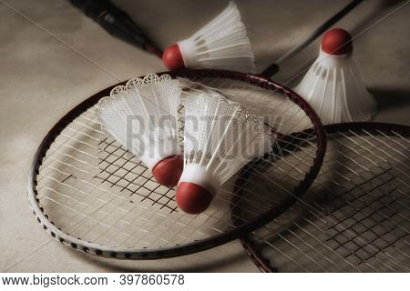 Two badminton rackets and shuttlecocks on gray surface with strong side light and shallow depth of field. Focus on top racket and birdie.