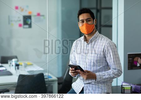 Mixed race man wearing face mask in an office. standing, looking at the camera and using digital tablet. hygiene in workplace during coronavirus covid 19 pandemic.