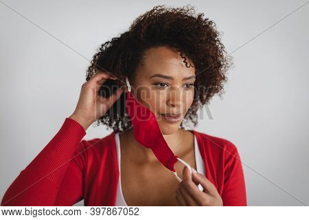 Portrait of african american woman removing face mask against grey background. hygiene and precautions for infection prevention during coronavirus covid 19 pandemic.
