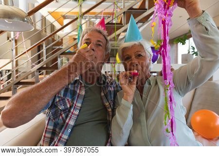 Senior caucasian couple on video call celebrating birthday. in party hats blowing party blowers. sitting in living room at home. self isolation during coronavirus covid 19 pandemic