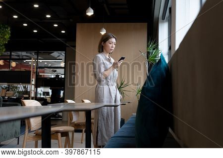 Asian woman using smartphone in creative office cafeteria. social distancing in business office workplace during covid 19 coronavirus pandemic.