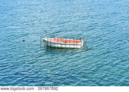 White And Red Wooden Rowboat Floating On The Sea. Rias Baixas, Galicia, Spain.