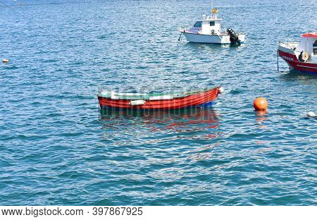 Camelle, Spain. September 19, 2020. Old Red Wooden Rowboat Floating On The Sea. Rias Baixas, Coruña