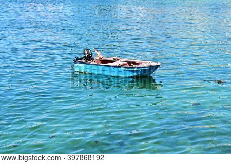 Portosin, Spain. July 3, 2020. Old Red And Blue Wooden Small Boat Floating On The Sea At Famous Rias