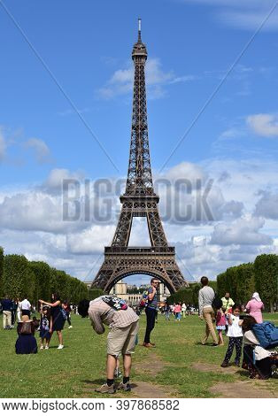 Paris, France. August 13, 2019.  Eiffel Tower With Tourists Having Fun And Taking Pictures From Cham