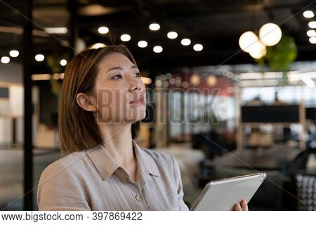 Asian businesswoman using digital tablet in creative office. social distancing in business office workplace during covid 19 coronavirus pandemic.