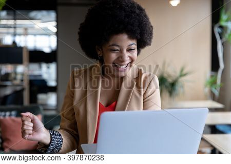 Cheering mixed race businesswoman using laptop during video call in office. technology and social distancing in business office workplace during covid 19 coronavirus pandemic.