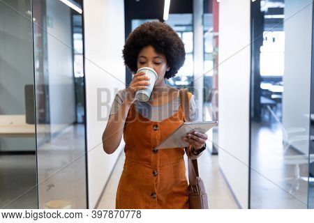 Mixed race businesswoman using tablet drinking coffee in creative office. technology and social distancing in business office workplace during covid 19 coronavirus pandemic.