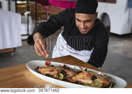 Male middle eastern chef adding salt over roasted fish dish in food plate at restaurant kitchen. food preparation restaurant culinary gourmet