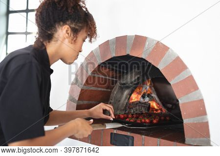 Mixed race female chef cooking in kitchen. female chef wearing black apron and preparing food.