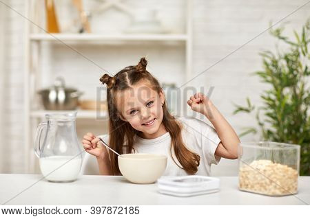 Adorable Little Girl Eating Breakfast: Cereal With The Milk In The Kitchen. Healthy Breakfast