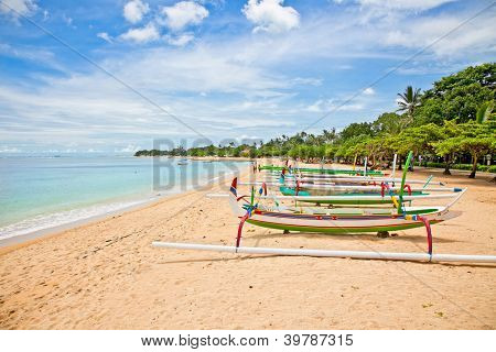 Beautiful tropical beach with fisherman's boats in Nusa Dua on Bali, Indonesia.
