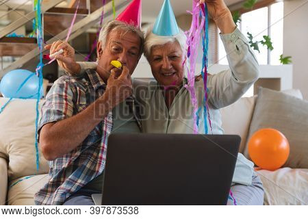Senior caucasian couple on video call celebrating birthday. in party hats blowing party blowers. sitting in living room at home using laptop. self isolation during coronavirus covid 19 pandemic