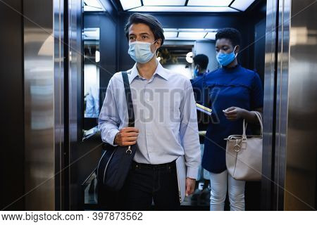 Diverse businessman and businesswoman wearing face masks in lift. social distancing and hygiene in creative office workplace during covid 19 coronavirus pandemic.