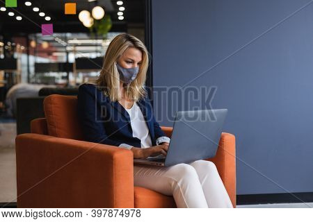 Caucasian businesswoman wearing face mask using laptop in creative office. social distancing in business office workplace during covid 19 coronavirus pandemic.