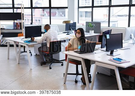 Mixed race businessman and businesswoman wearing face masks working in office. social distancing in business office workplace during covid 19 coronavirus pandemic.