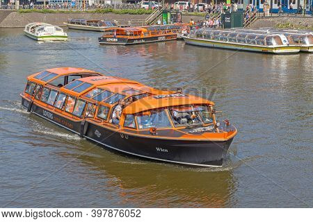 Amsterdam, Netherlands - May 14, 2018: Lovers Canal Cruises Orange Boat In Amsterdam, Holland.