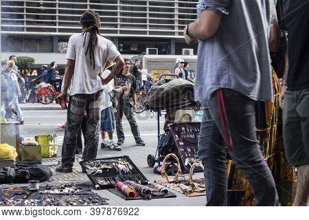 Sao Paulo / Sao Paulo / Brazil - 08 19 2018: Black Man With Hair Full Of Dreads Selling His Merchand