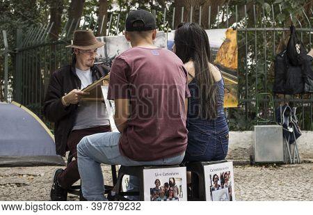 São Paulo / São Paulo / Brazil - 08 19 2018: Artist Drawing Caricatures Of An Asian Couple