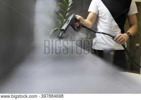 Worker Of A Cleaning Company Is Cleaning The Tiles In The Bathroom With Steam. Hot Steam Cleaning An
