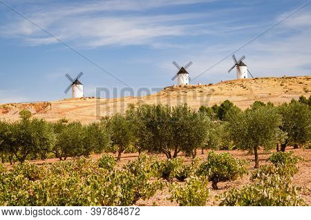Three Old Windmills On A Hill In Alcazar De San Juan, Castile La Mancha, Spain.