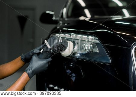 Car Wax Polishing Process. Cropped Close Up Image Of Hands Of Male Professional African Worker In Pr