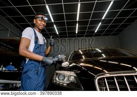 Smiling Handsome Young Black Man, Professional Worker Of Car Detailing Service, Polishing Black Car