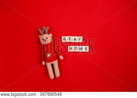 Letters Stay At Home On Red Background With Snowflakes And Amigurumi Deer. Coronavirus Protection Co