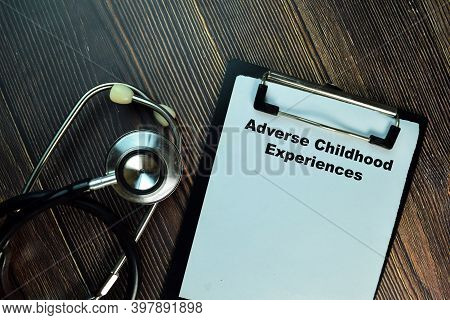 Adverse Childhood Experiences Write On A Paperwork Isolated On Wooden Table. Medical Or Healthcare C