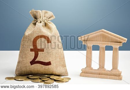 British Pound Sterling Money Bag And Bank / Government Building. Budgeting, National Financial Syste