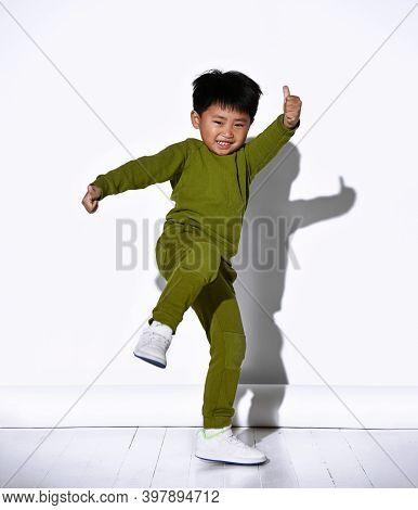 Fashion Portrait Of Cute Little Kid Boy In Stylish Green Tracksuit Dancing Break Against White Studi