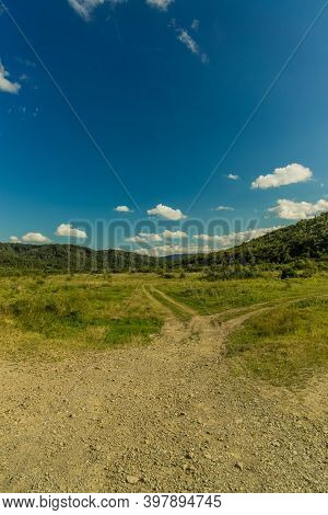 Vertical Picture Of Country Side Rustic Outskirts Environment Space Field With Car Tire Mark