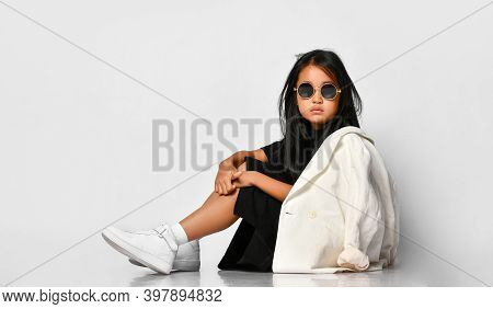 Side View Of Little Stylish Girl Model Posing In Studio Wearing Sunglasses And Looking Straight. The