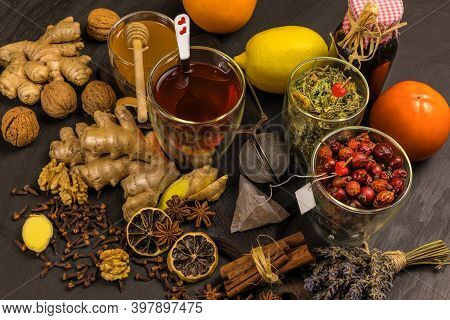 Ginger Tea In A Cup On Black Wooden Background. Cinnamon And Star Anise With Cloves. Treatment Of Fl