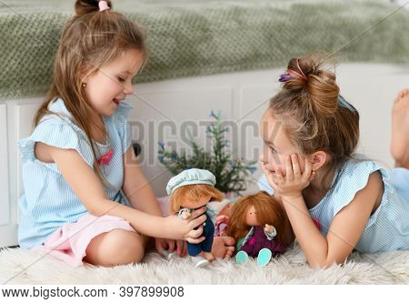 Cheerful Pretty Small Girls Sisters Kids With Long Hair In Same Clorhing Playing With Toys Dolls Tog