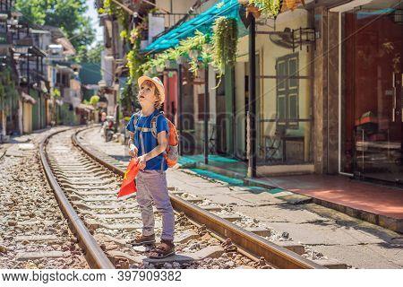 Boy Traveler Walk Around Railway Paths Which Go Through Residential Area In Hanoi City. Hanoi Train