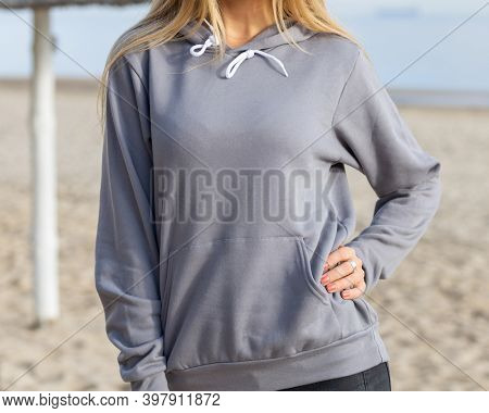 Front view of unrecognizable woman standing in grey hoodie. She is posing to camera on beach, outdoor. Close view of blouse with copy space.